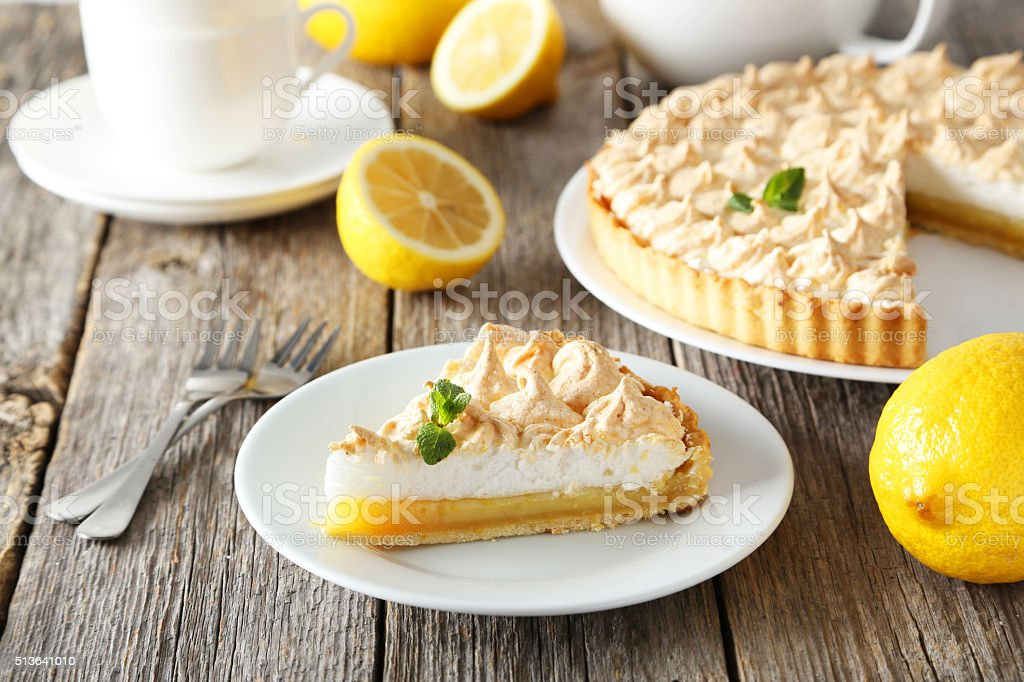Lemon meringue pie on plate on grey wooden background stock photo