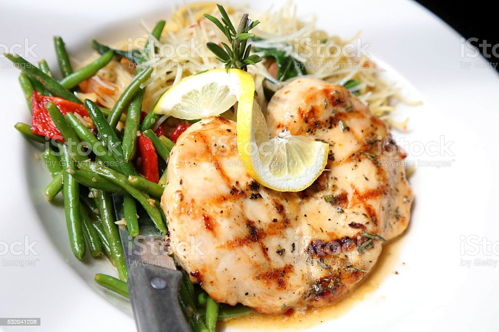 Lemon Rosemary Chicken On Plate Of Spaghetti And Green Beans stock photo