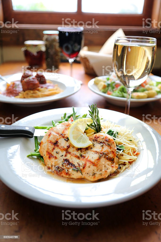 Lemon Rosemary Chicken Plate Accompanied By A Goblet Of Wine stock photo
