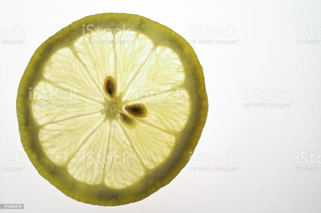 Lemon slice closeup on a light table (back lighted) royalty-free stock photo