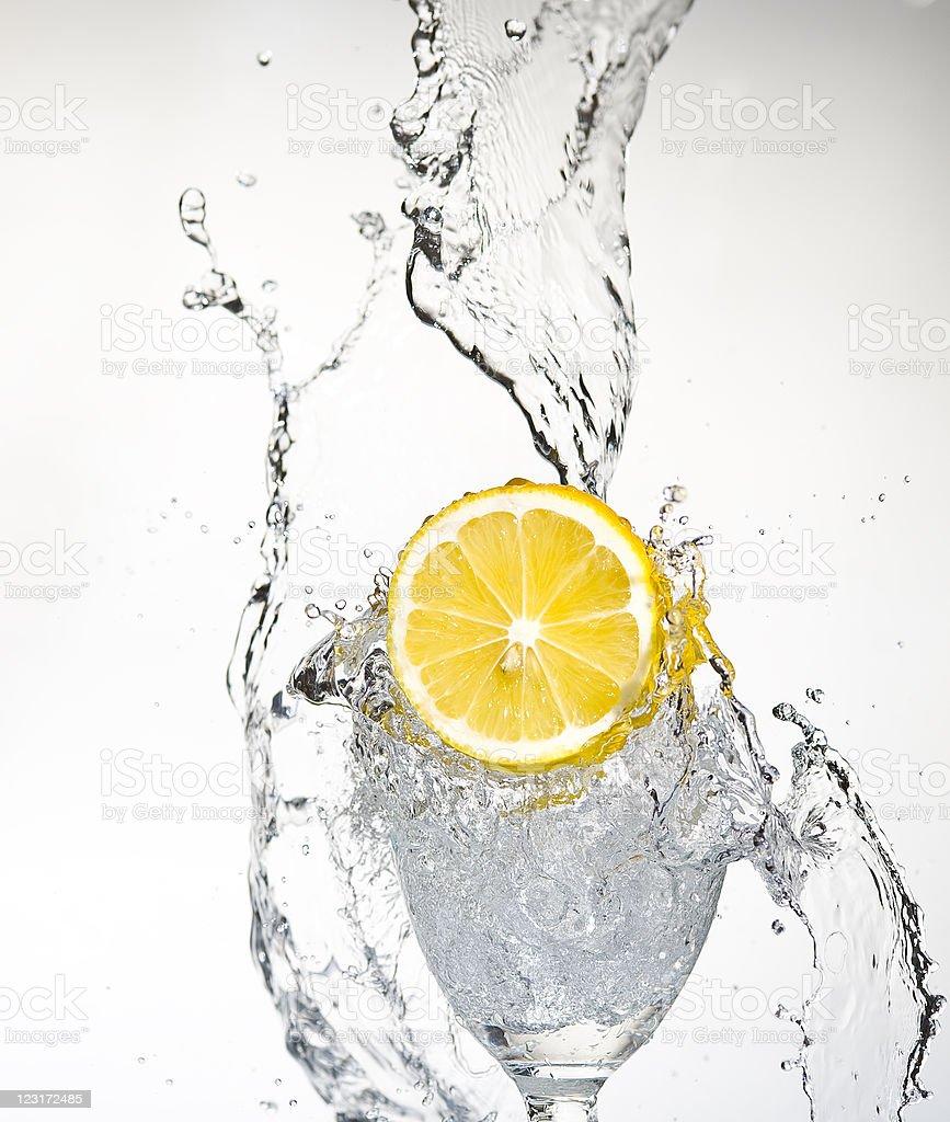 A lemon slice dropping into water splashing stock photo