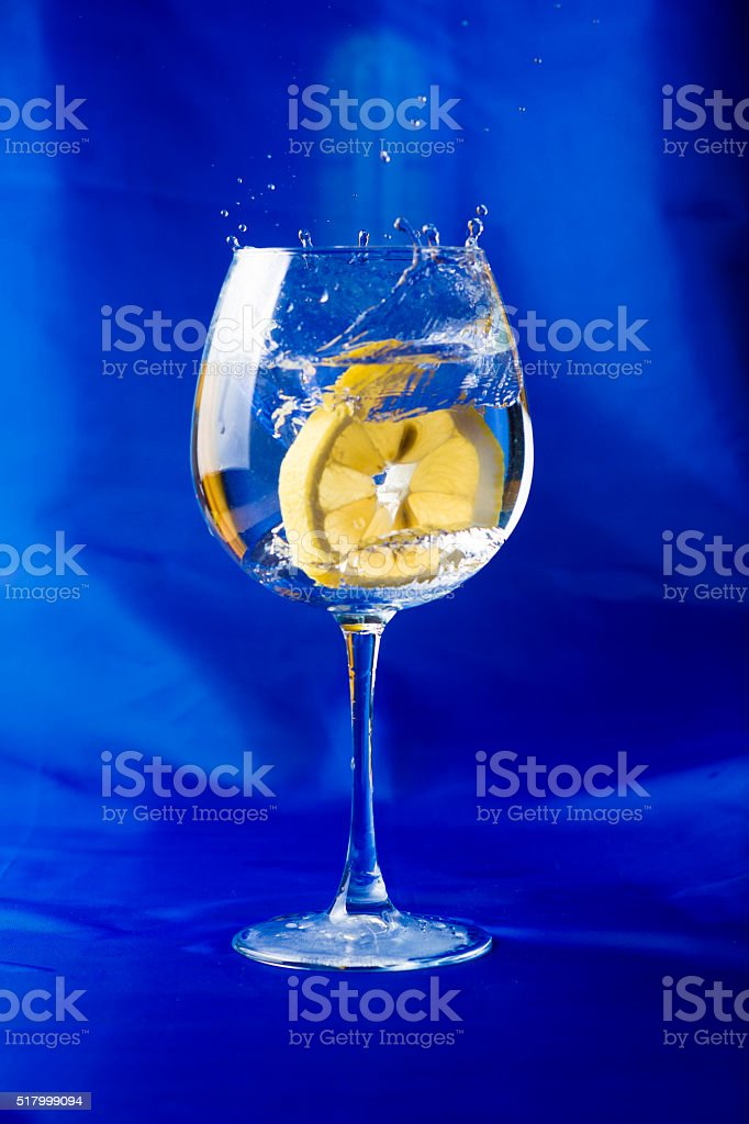 lemon slice thrown into a glass of water stock photo