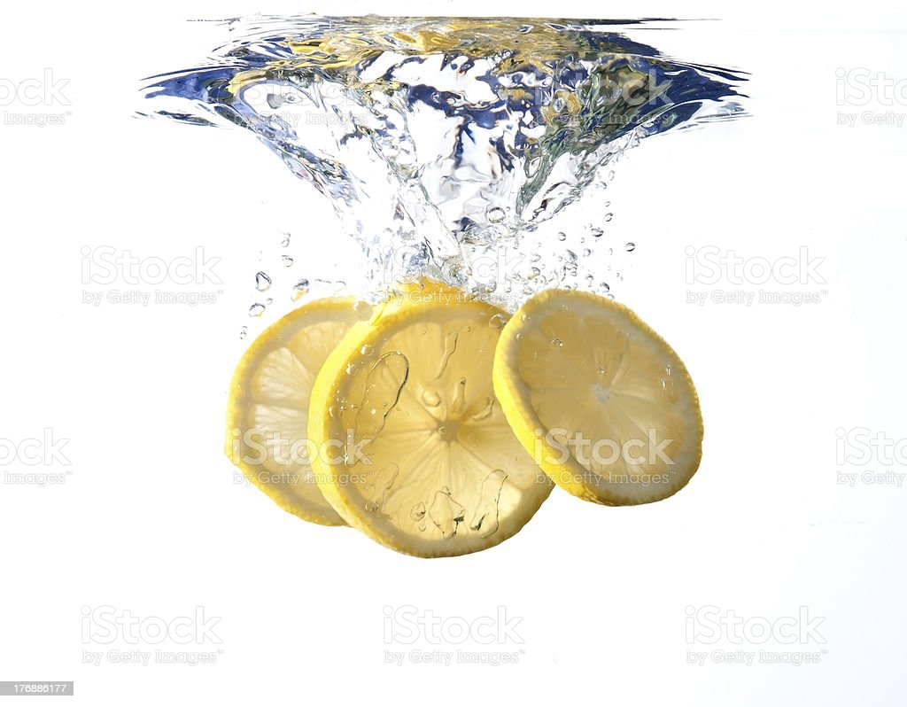 Lemon slices fall into water royalty-free stock photo