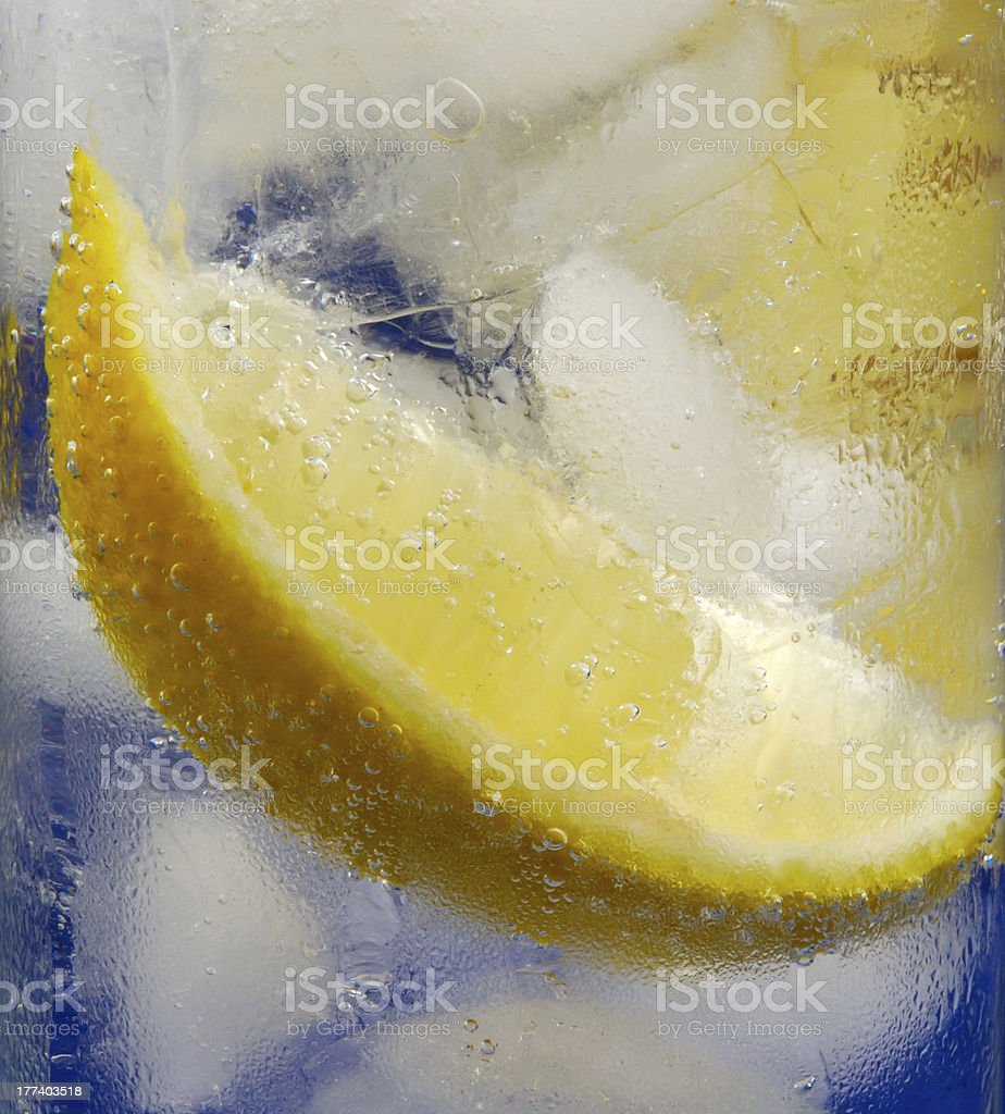 Lemon Wedge in Glass of Cold Mineral Water with Ice royalty-free stock photo