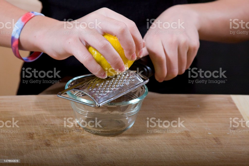 Lemon zest being grated into glass bowl stock photo