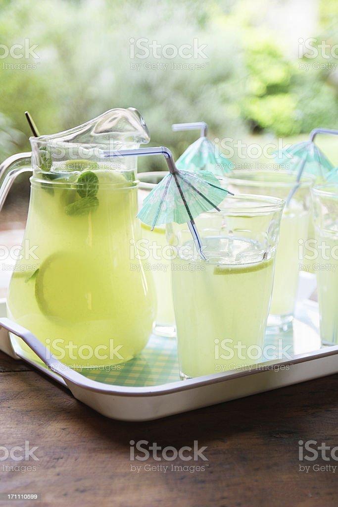 Lemonade cocktail with umbrella drinking straws at garden royalty-free stock photo