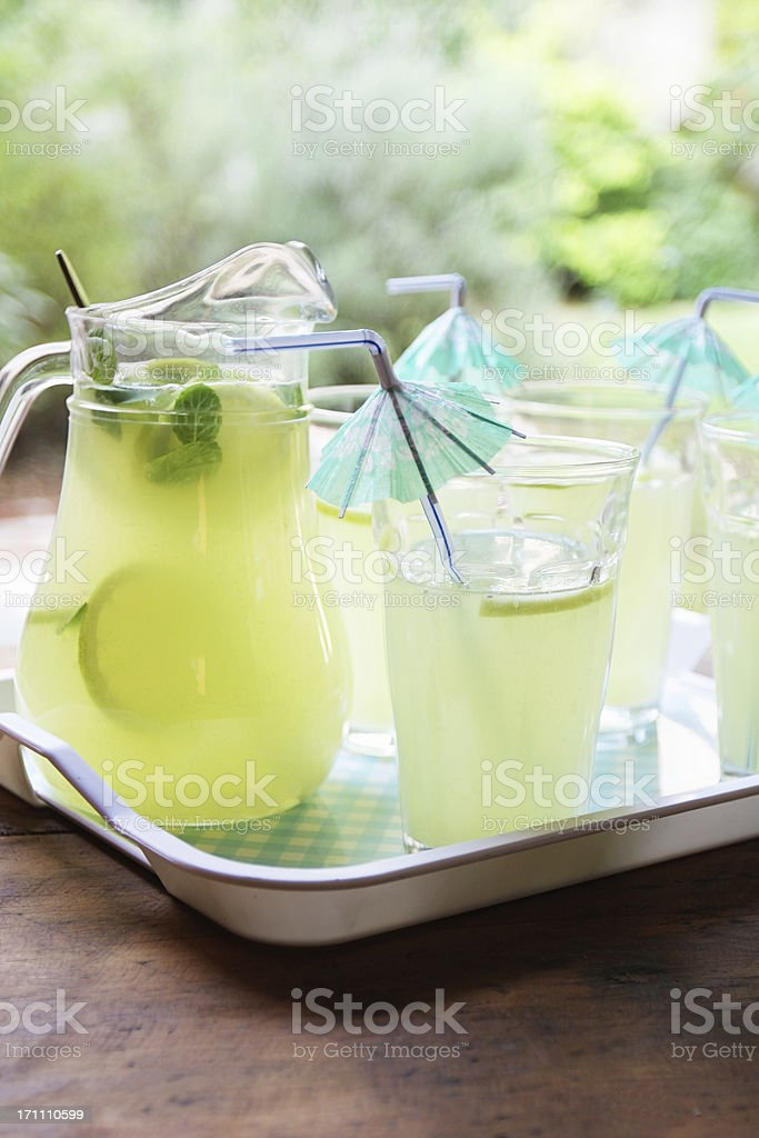 Lemonade cocktail with umbrella drinking straws at garden stock photo