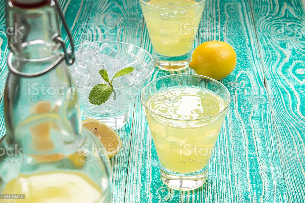 lemonade or limoncello on turquoise colored wooden table stock photo