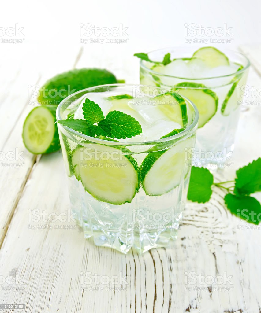 Lemonade with cucumber and mint on light board stock photo