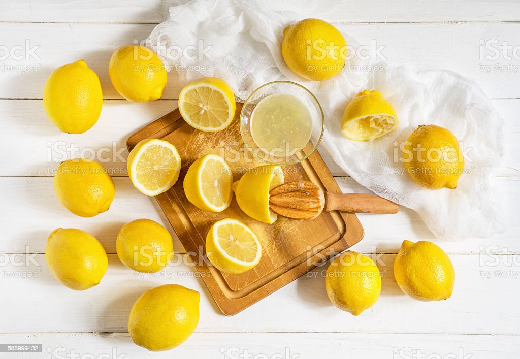 Lemons and citrus squeezer on a wooden background stock photo