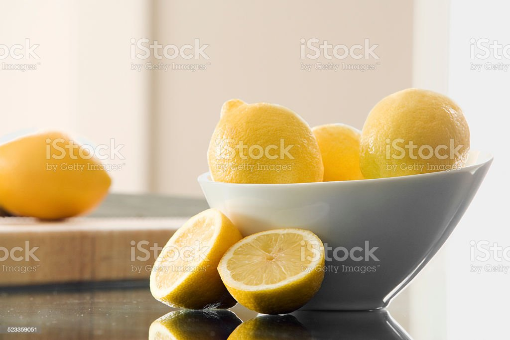 Lemons in a bowl and cut up on counter stock photo