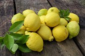 Lemons in a pile on a weathered wood plank table