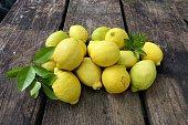 Lemons in pile on wooden table