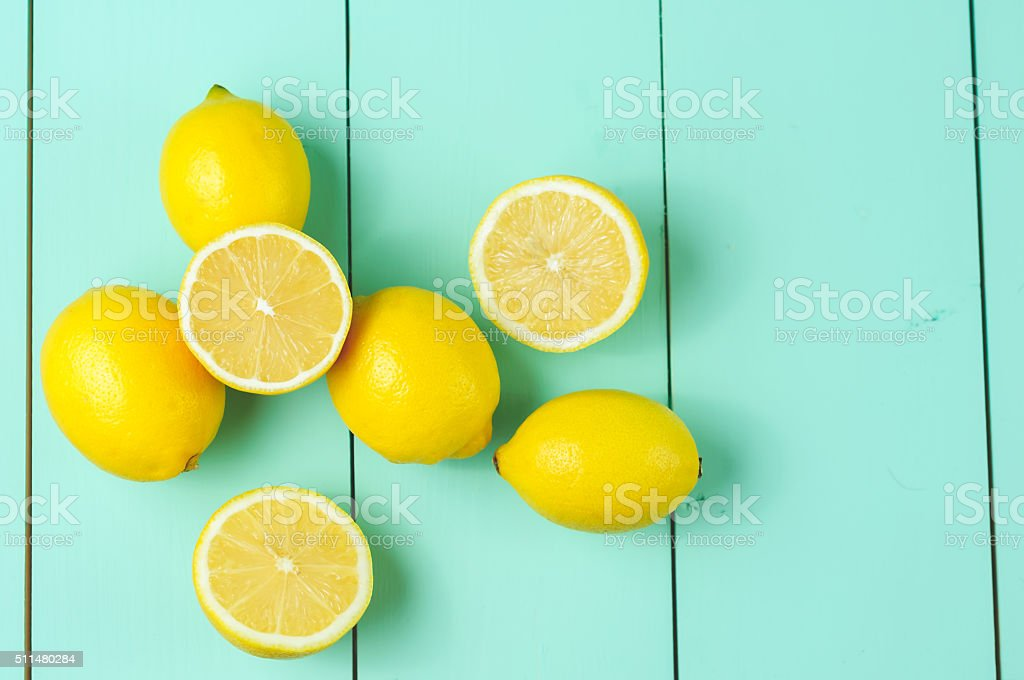 Lemons scattered on a blue wooden background. stock photo