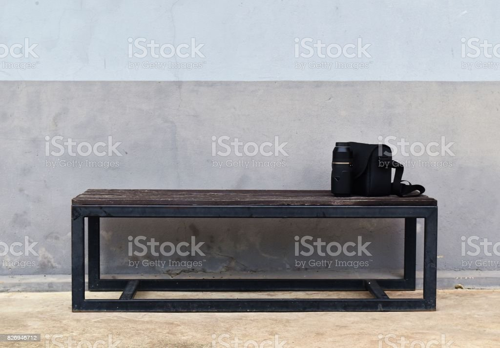lens and camera bag on steel long bench in front of dirty gray old wall for waiting to work in working day stock photo
