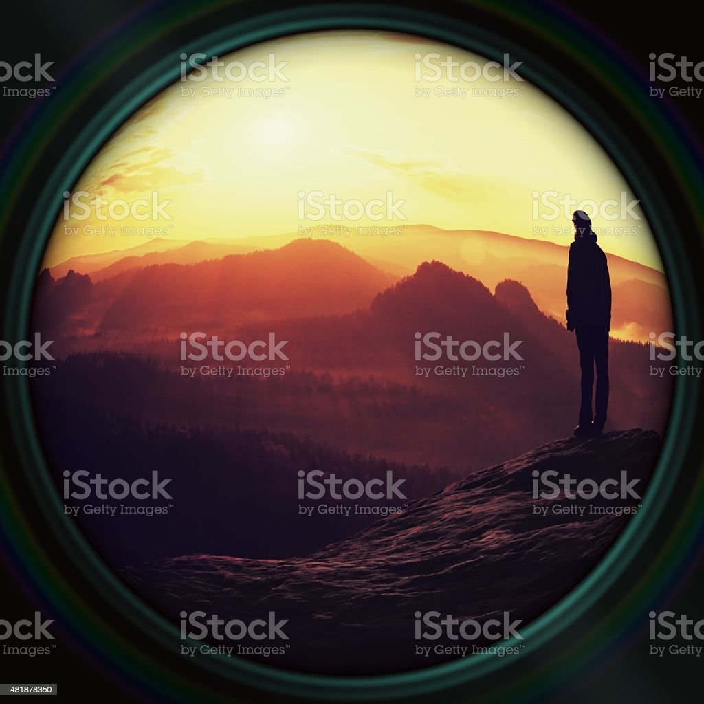 Lens effect. Alone hiker on empire rick, valley and Sun stock photo