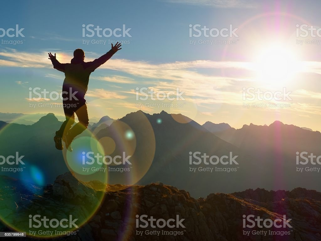 Lens effect. Bow light circles. Hiker jumping at  mountain peak. stock photo