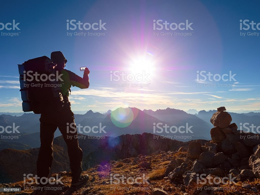 Lens flare defect. Hiker takes selfie photo with big backpack stock photo