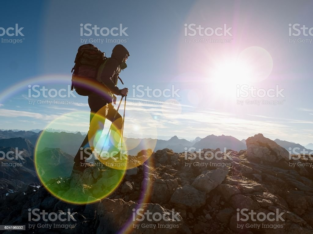 Lens flare defect.  Silhouette with hodd, backpack and poles stock photo