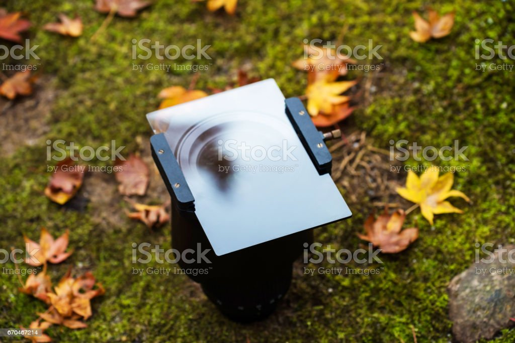 Lense with Graduated Neutral Density (GND) filter and holder for autumn stock photo