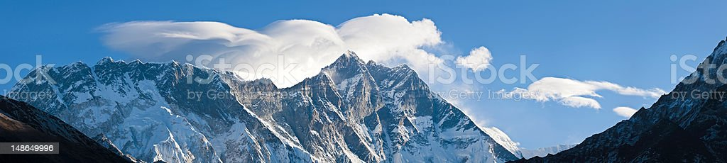 Lenticular cloud waves breaking over mountain peaks panorama Himalayas Nepal stock photo