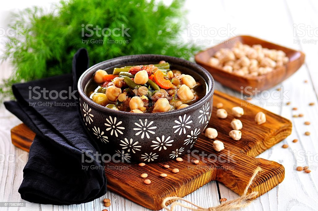 Lentil soup with chickpea, bacon, onion, carrot, green beans, garlic stock photo