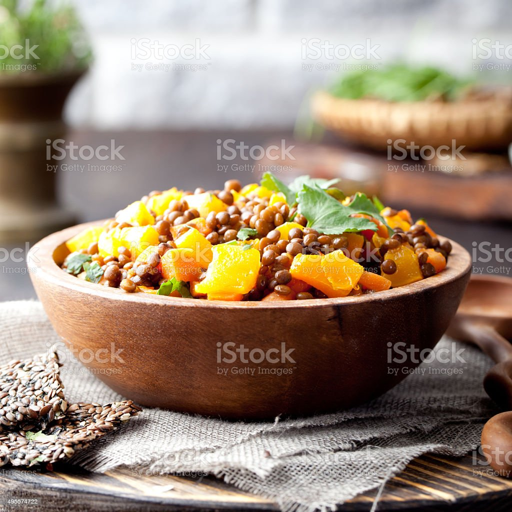 Lentil with carrot and pumpkin ragout in a wooden bowl. stock photo