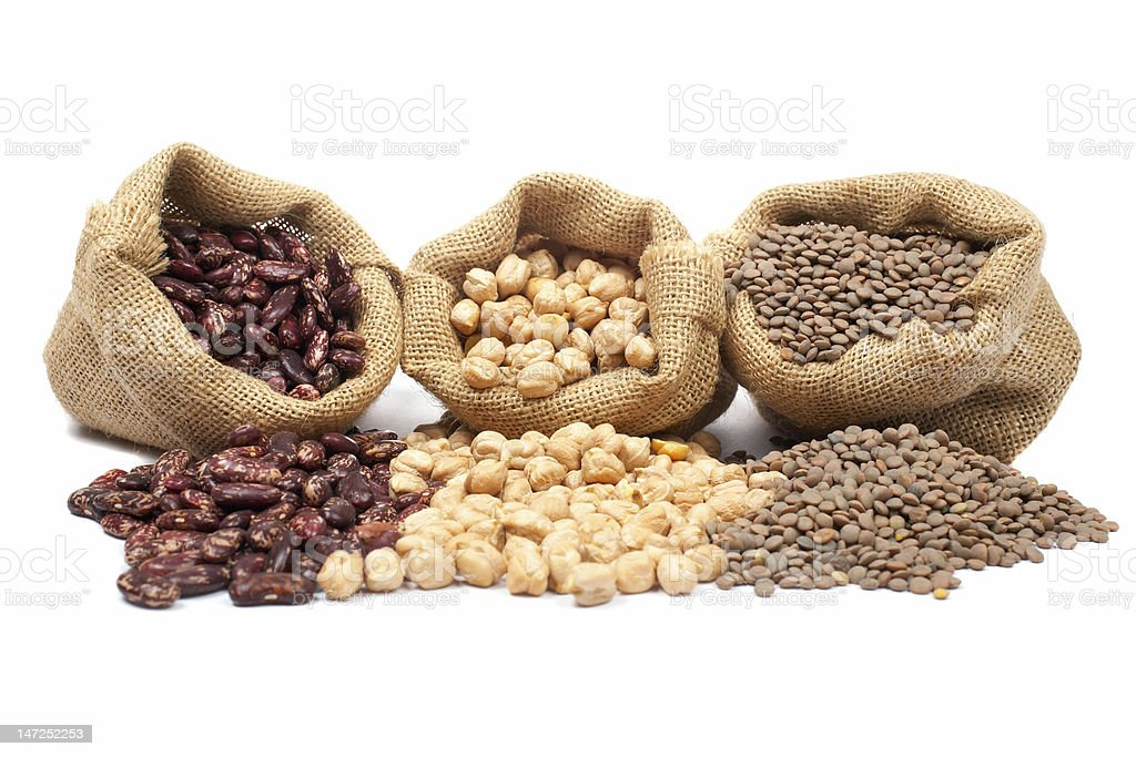 Lentils, chickpeas and red beans spilling out of burlap bags stock photo