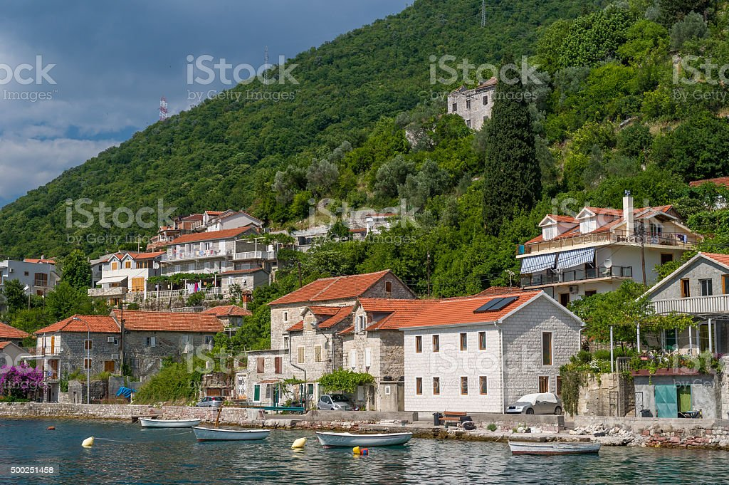 Lepetane old town under the mountains.Eembankment view from water stock photo