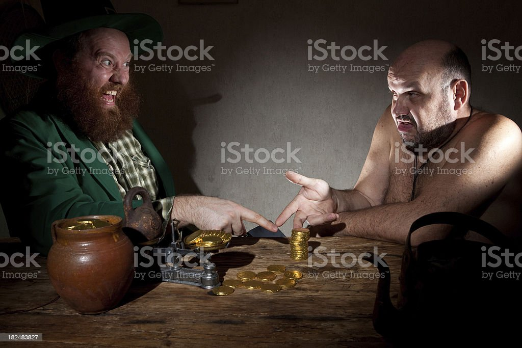 Leprechaun and Ogre divide coins stock photo