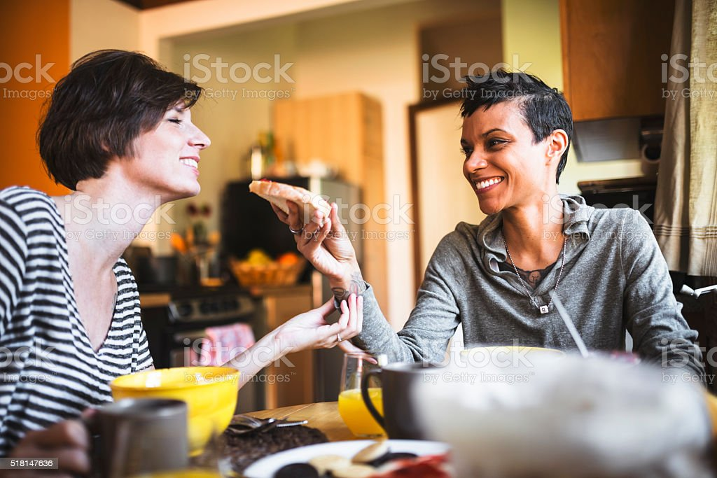 lesbian couple doing breakfast on the kitchen togetherness stock photo
