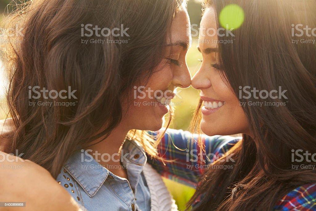 Lesbian couple embrace touching noses, eyes closed, close up stock photo