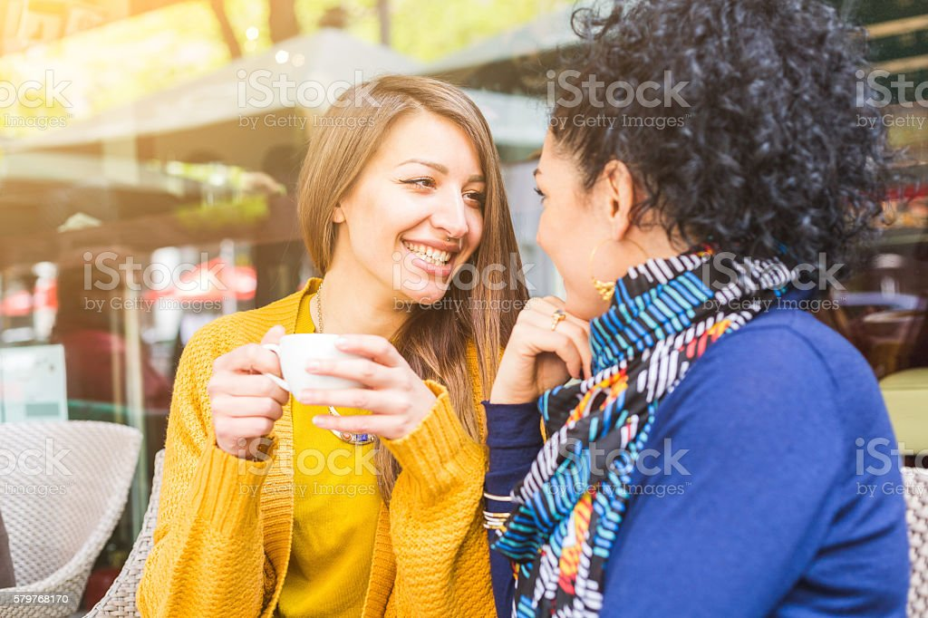 Lesbian couple having a coffee at a cafe stock photo