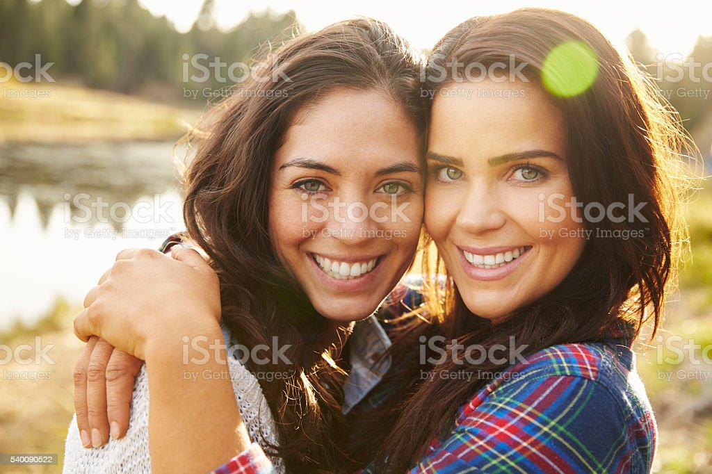 Lesbian couple hugging by a lake look to camera, close stock photo
