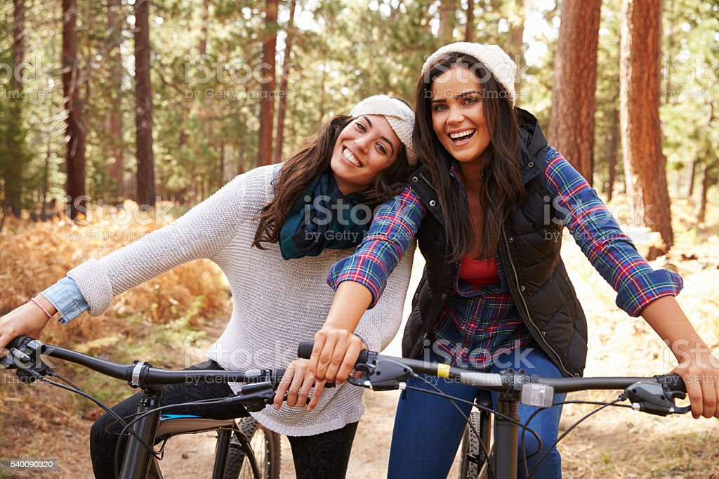 Lesbian couple on bikes in a forest look to camera stock photo