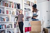 Lesbian couple unpacking cardboard box in living room