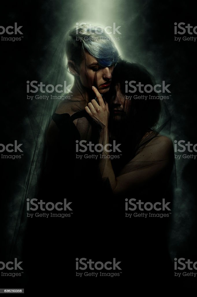 Lesbian Lovers Embracing Under Melodramatic Light stock photo
