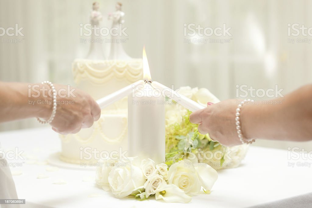 Lesbian Same Sex Marriage Brides Lighting Candle with Wedding Cake royalty-free stock photo