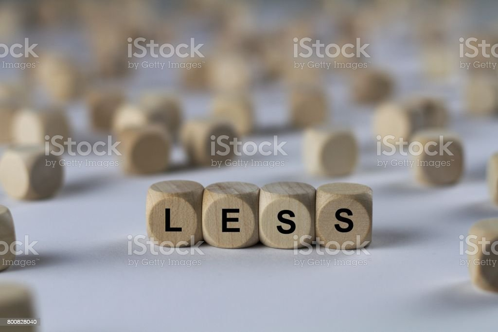 less - cube with letters, sign with wooden cubes stock photo