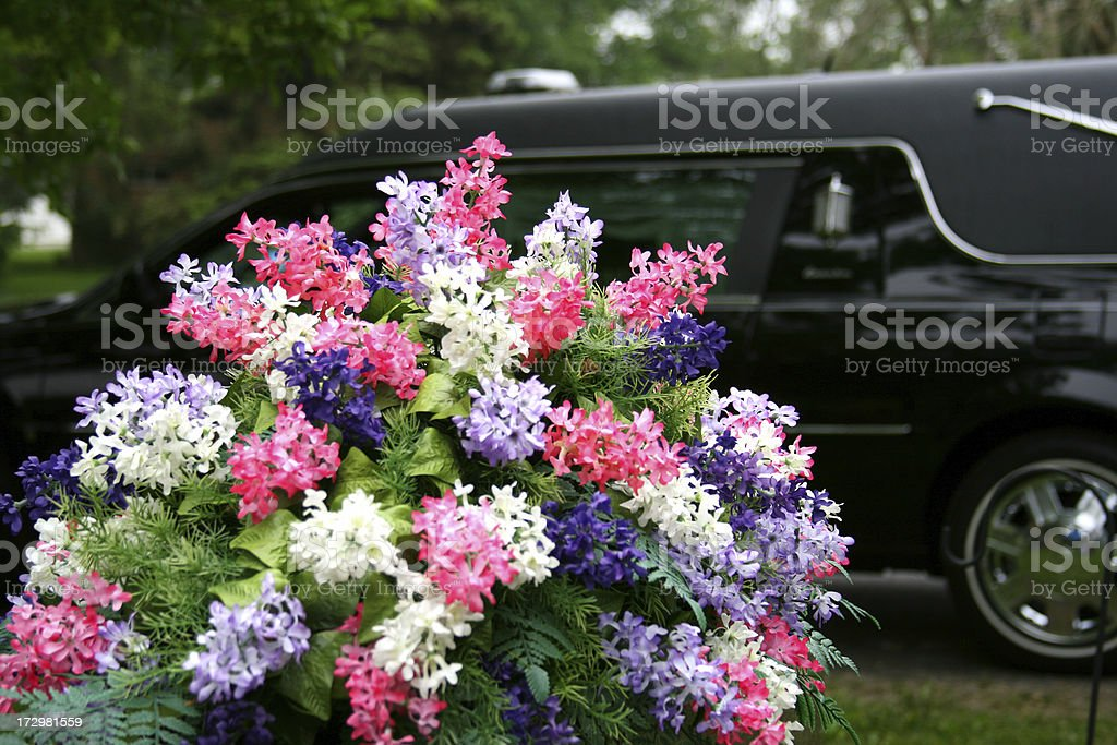 Lesson in Contrasts - Vibrant flowers and Funeral Hearse stock photo
