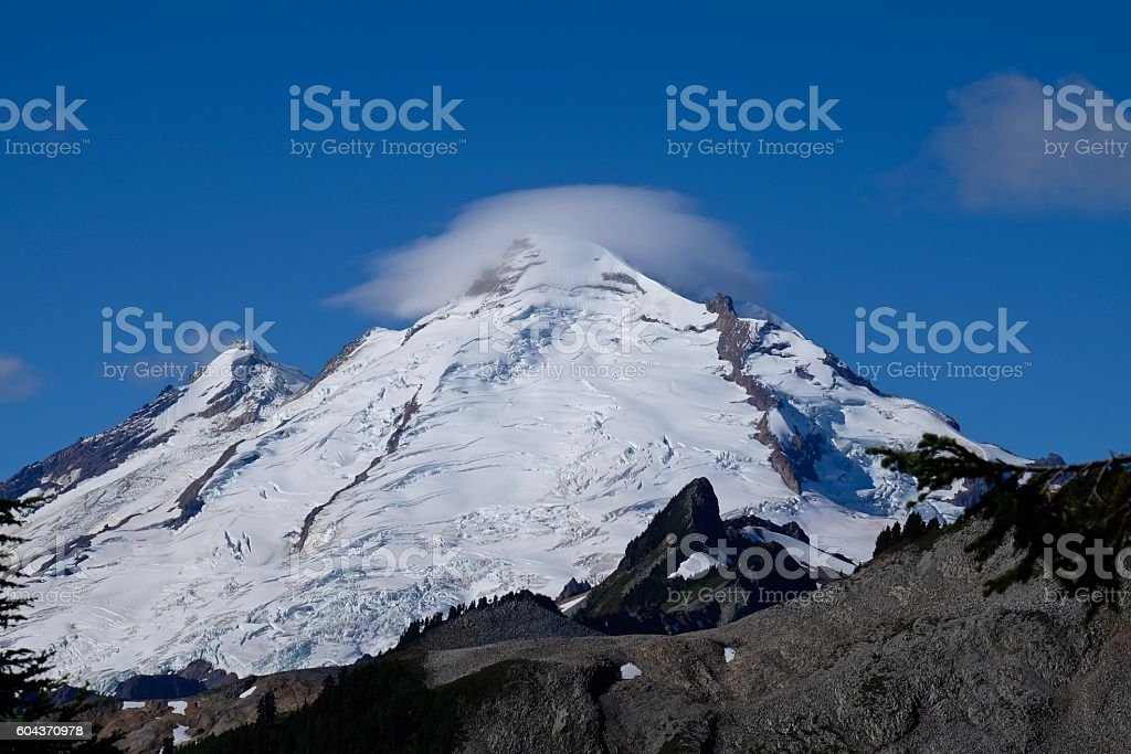 Leticular clouds over mountain top. stock photo