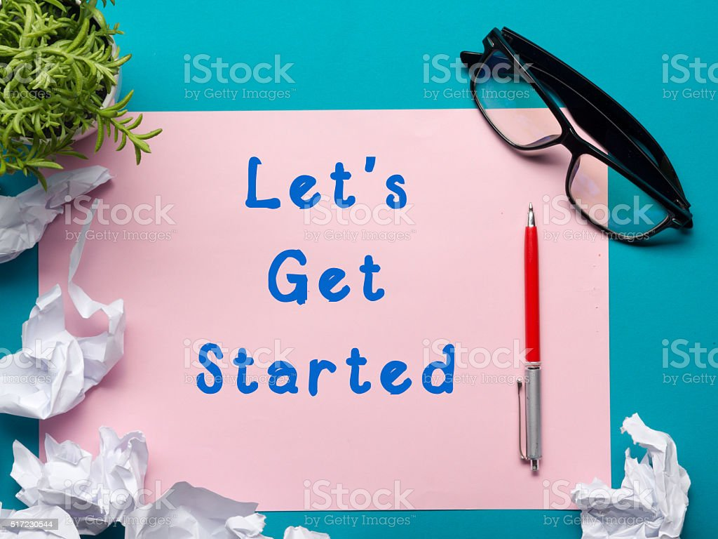 Let's get started message - Office desk table with stock photo