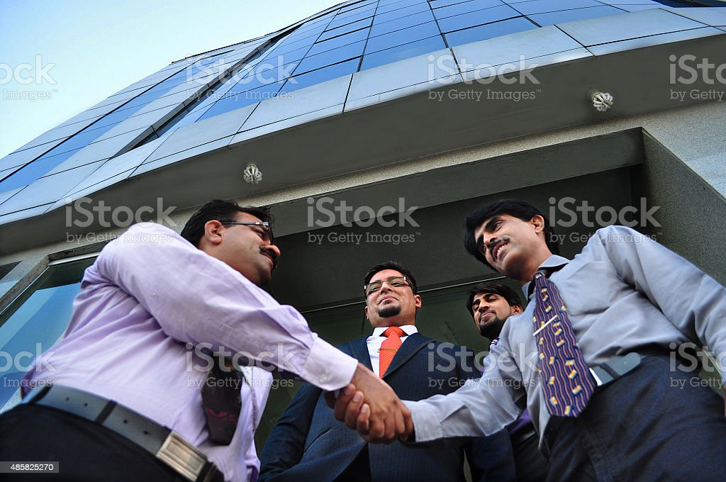 Lets shake hands and come closer in business under roof stock photo