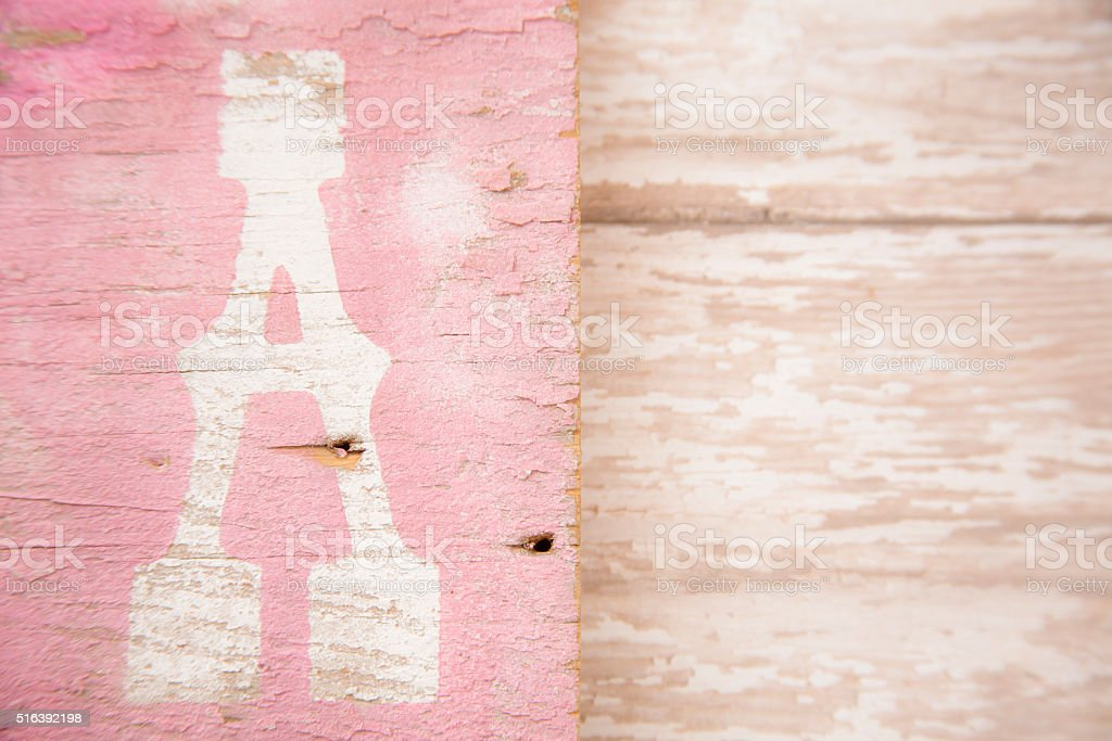 Letter 'A' on rustic wooden background. Pink, tan. stock photo