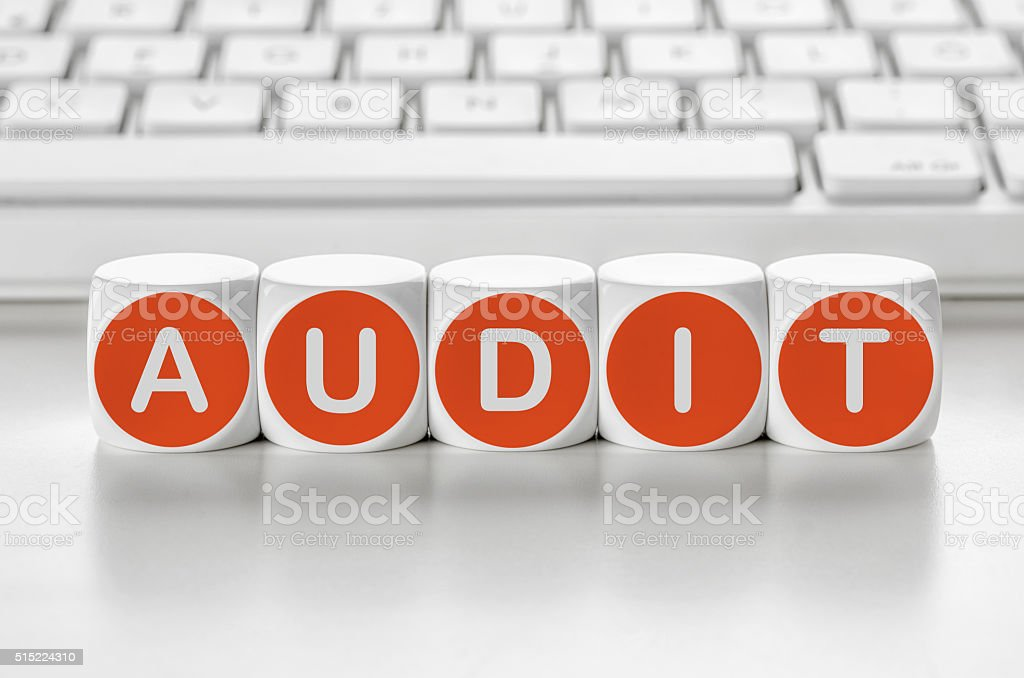Letter dice in front of a keyboard - Audit stock photo