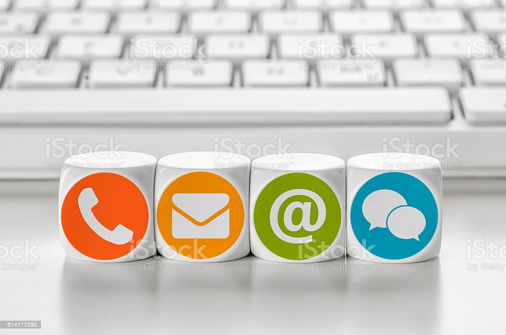 Letter dice in front of a keyboard - Contacting stock photo