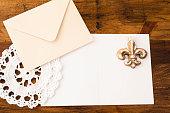 Letter, envelope, doiley, fleur de lis on wooden table.