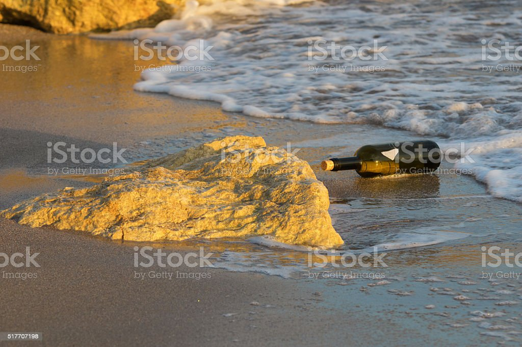 letter in a bottle on the beach stock photo