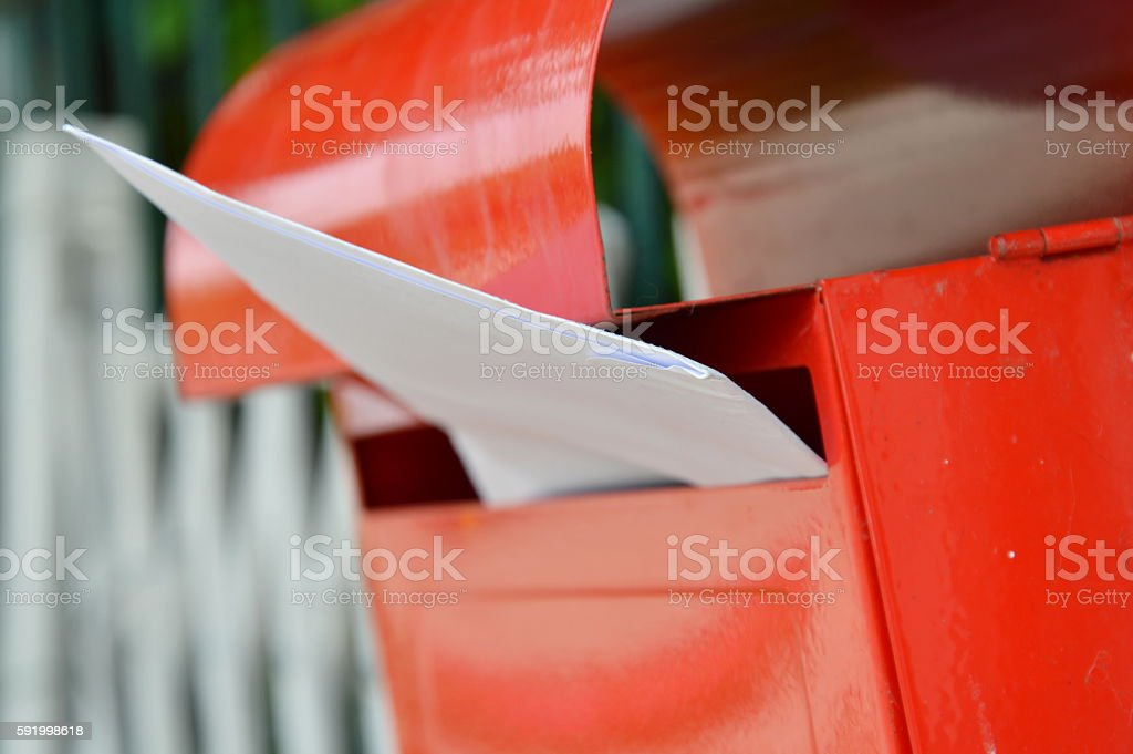 letter in red mail box on home fence stock photo
