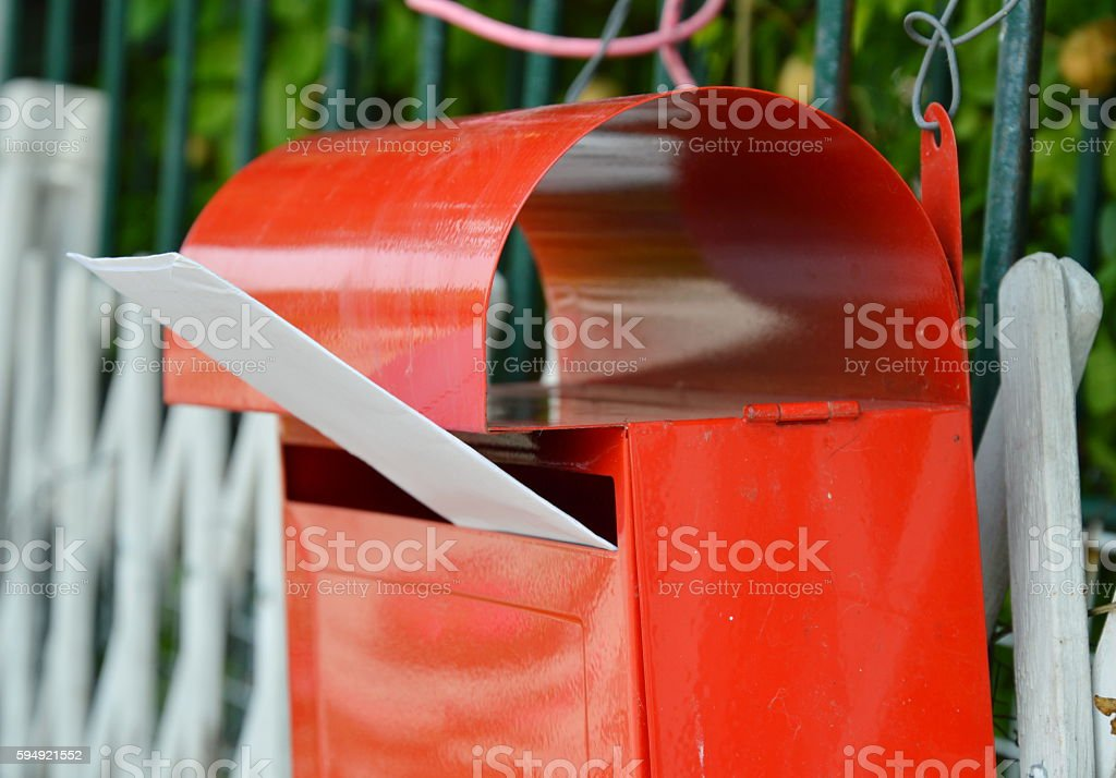 letter in red post box on home fence stock photo